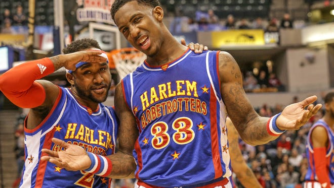 Dizzy, left, and Bull, right, pose for photos during game play, Jan. 14, 2017. The Harlem Globetrotters took on the World All-Stars at Bankers Life Fieldhouse in Indianapolis.
