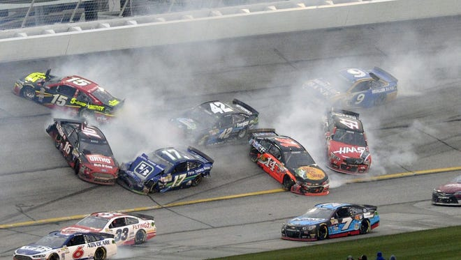 Drivers Greg Biffle (16), Ricky Stenhouse Jr. (17), Clint Bowyer (15), Kyle Larson (42), Tony Stewart (14), Regan Smith (41) and Trevor Bayne (6) crash during the NASCAR Sprint Cup series auto race at Atlanta Motor Speedway, Sunday, March 1, 2015, in Hampton, Ga.