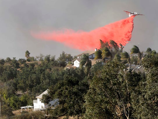 A CalFire tanker drops retardant on a portion of the