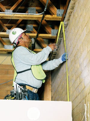 Construction worker Gabriel Alaman takes measurements lastg year at the Mesilla Public Safety Building.
