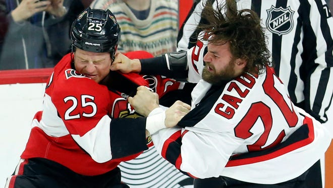 Senators' Chris Neil (25) fights with Devils' Luke Gazdic (20) during first-period action in Ottawa, Ontario, Saturday, Dec. 17, 2016.