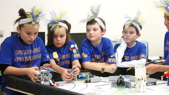 Team members of the Buena Vista Superheroes, from Buena Vista Elementary, ready their robot for the judges.