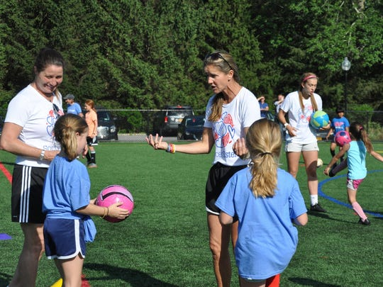 Brandi Chastain gives pointers to kids at a soccer