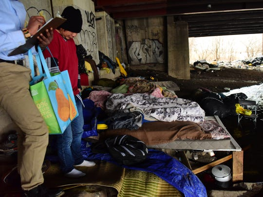 Tristan Anderson, a volunteer for the annual Point in Time count of the homeless in Bergen County, talks to a homeless man sleeping under the Route 46 Bridge at the Overpeck Creek.
