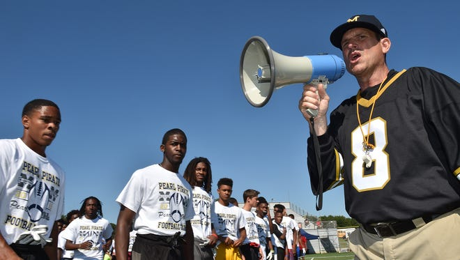 Michigan football coach Jim Harbaugh encourages the more than 500 high school football players in their speed drill, Wednesday at a Michigan Satellite Camp at Pearl High School in Pearl, Miss.