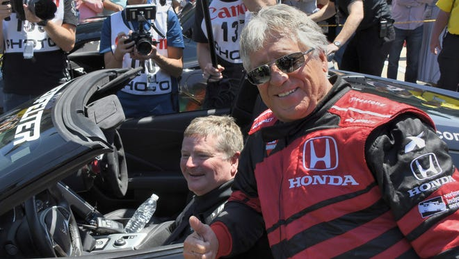 Sam Schmidt and Mario Andretti celebrate after the completion of the semi-autonomous car race prior to the IndyCar Grand Prix at the Indianapolis Motor Speedway on May 13, 2017.