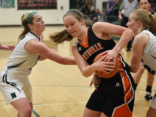 Mustang Bryce Quick, center, tries to keep a rebound away from two Wildcats including Julia Lalain, left, during the teams' Feb. 10 match at Novi High.