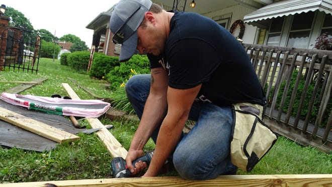 Jake Powell, Chillicothe firefighter and founder of 2B3N Ministry, drills a screw into a wheelchair ramp at a residence on Knoles Avenue Friday afternoon.