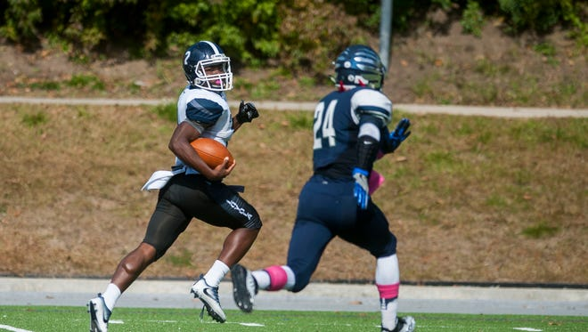 Detroit Loyola's Price Watkins (2) rushes the ball being pursued by Bloomfield Hills Cranbrook's Aaron Wiggins (24) during Loyola's 30-3 win over Cranbrook on Saturday in Bloomfield Hills.