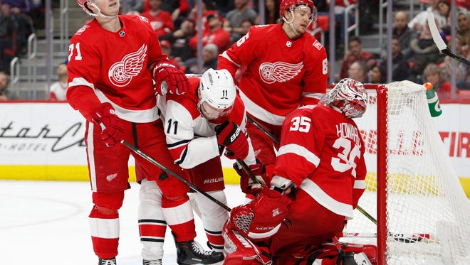 Red Wings goaltender Jimmy Howard (35) center Dylan Larkin (71) and defenseman Danny DeKeyser (65) react after Hurricanes right wing Justin Williams (not pictured) scores a goal during the third period of the Wings' 3-1 loss on Saturday, Jan. 20, 2018, at Little Caesars Arena.