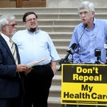 Indiana Rep. Ed Delaney (at podium), a Democrat from Indianapolis, speaks Aug. 26, 2013, to about 20 people, plus the news media, on the south steps of the Indiana Statehouse promoting the federal Affordable Care Act. State Sen. Tim Lanane (left), a Democrat from Anderson, and Jeremy Bernstein (center), a 41-year-old from Goshen who is a community organizer for Americans for Democratic Action, also spoke.