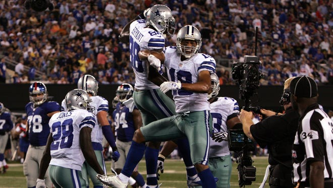 Cowboys wide receiver Miles Austin (19, facing) celebrates TD catch with teammate Dez Bryant (88) in the fourth quarter to give Dallas a 24-10 lead during the 2012 season opener at MetLife Stadium. This is Austin's seventh of his eight seasons in the Cowboys franchise.