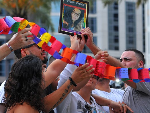 Victims Amanda Alvear photo is held up over the crowd