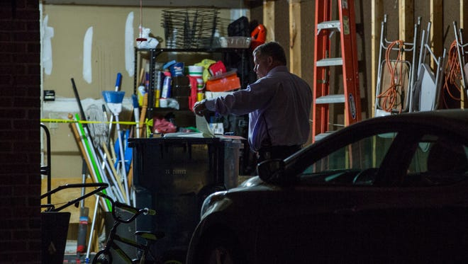A detective stands in the garage connected to the home where a 2-year-old boy died from a self-inflicted gunshot wound on April 20, 2016.