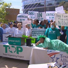 With a symbolic Lady Liberty dying on the table in the foreground, protesters outside the Dallas Omni hotel where Texas Gov. Rick Perry was speaking shouted their support for Medicaid expansion.