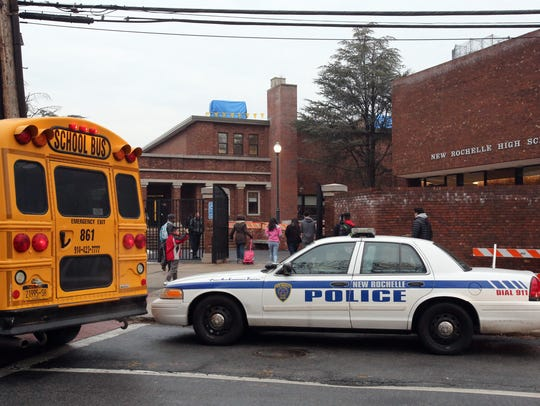 Students arrive for midterms as a police officer stands
