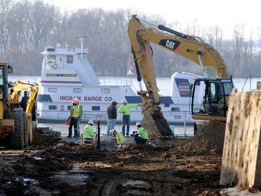 As a barge pushes a load downstream a swollen Ohio River, Garney Construction workers work on sewer pipes at the intersection of Second and Water streets in March 2011.