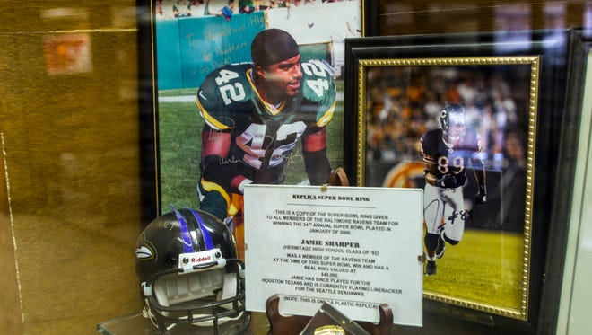 A photo of Darren Sharper (left) in his Green Bay Packers uniform is among the Sharper memorabilia in a trophy case at Hermitage High School in Henrico, Va. The school has decided to leave the display up for now, pending resolution of four rape charges against Sharper, two in Arizona and two in California.