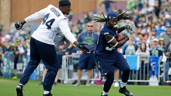 Seattle Seahawks running back Alex Collins, right, spins around defensive end Ryan Robinson (44) as he carries the ball during NFL football training camp, Saturday, Aug. 6, 2016, in Renton, Wash.