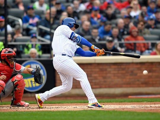 New York Mets shortstop Amed Rosario (1) hits an RBI single in the first inning. New York Mets face the St. Louis Cardinals on Opening Day at Citi Field in Flushing, NY on Thursday, March 29, 2018.