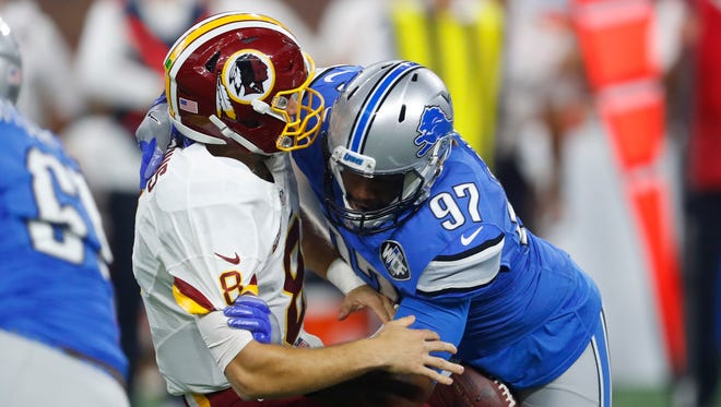 Washington Redskins quarterback Kirk Cousins (8) temporarily loses control of the ball after a hit by Detroit Lions linebacker Armonty Bryant (97) on Oct. 23, 2016 in Detroit.