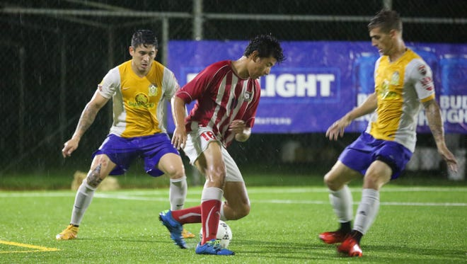 The Strykers FC's Xavier Naputi attempts to get the ball through the defense of Rovers FC's Jonahan Romero (left) and Logan Dillenburger (right) during a final round match of the Budweiser Futsal League Wednesday evening at the Guam Football Association National Training Center futsal courts. The Strykers won 5-4.