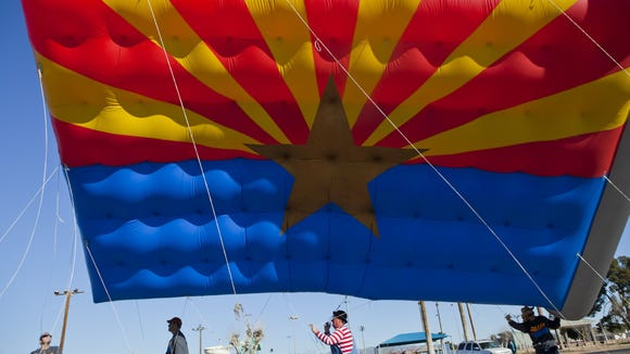 0128121023jy PNI0201-swv cattle drive - 1/28/12 - The large inflatable Arizona state flag makes its way through downtown Buckeye for the Buckeye Days Arizona Centennial Celebration Saturday morning Jan. 28. Photo by Sean Ryan/The Arizona Republic