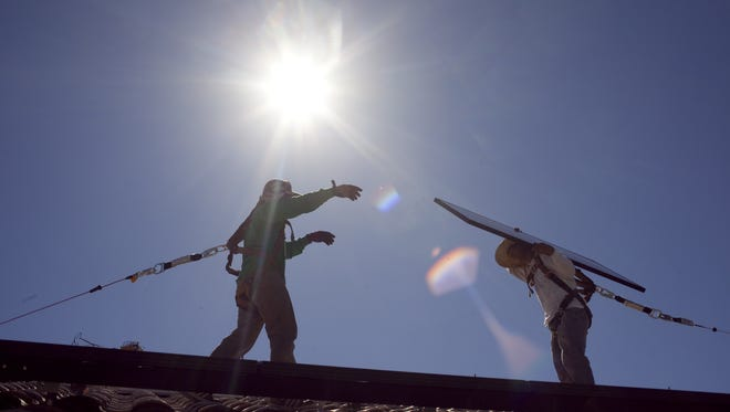 SolarCity employees work on the rooftop of a north Phoenix home.