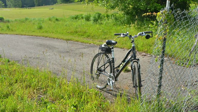 A bike resting near a fence by Kalamazoo County's Markin Glen Park on Wednesday, June 8, 2016. Five bicyclists were killed and four others seriously injured after being struck by a pickup truck near this site Tuesday evening, June 7, 2016.