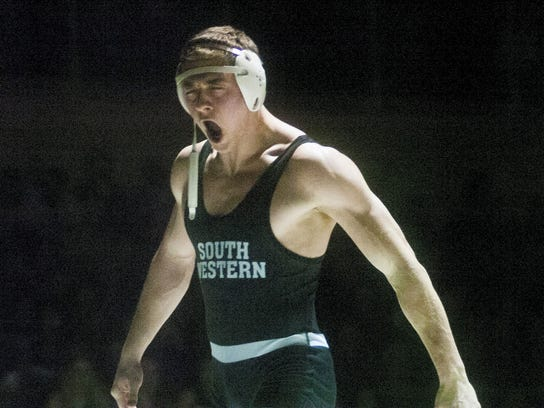 South Western's Logan Bowman howls in celebration after winning the 195-pound bout during last year's match against Spring Grove. Bowman pinned the Rockets' Joshua Cribbs in 54 seconds, and the Mustangs earned a 34-27 victory. South Western's win created a three-way tie atop Division I with Spring Grove and New Oxford. (Shane Dunlap -- GameTimePA.com)