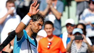 Rafael Nadal waves to the crowd while leaving the court