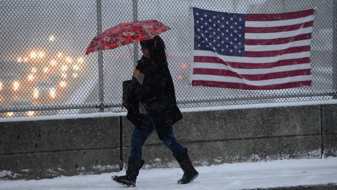 A woman walks in the snow toward the Wood-Ridge train station on Moonachie Ave over Route 17 Thursday.