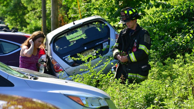 A woman inspects the damage to her parked car after a man driving his car tried to park at the YMCA on the first day of summer camp when he claimed to police that his brakes failed to work on Monday June 25, 2018.