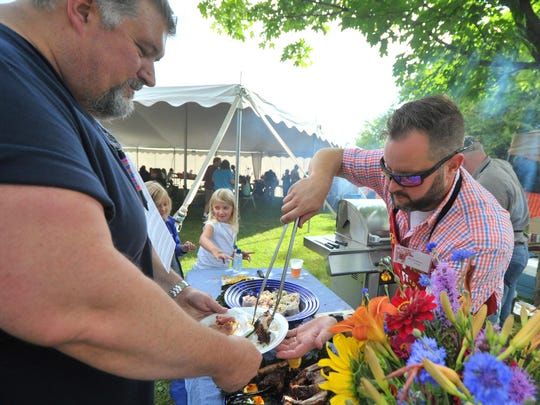 In this 2014 file photo, Chef Eric Budleski, right, of Hatley serves a rib he grilled to Chris Morgan during the Guys Who Grill event at Riverside Park in Wausau.