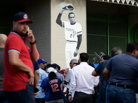 A mural of Puerto Rican professional baseball right fielder Roberto Clemente decorates Hiram Bithorn Stadium where fans wait to enter the final game of a two-game Mayor League Series between the Minnesota Twins and the Cleveland Indians in San Juan, Puerto Rico, Wednesday, April 18, 2018. (AP Photo/Carlos Giusti) ORG XMIT: CGPR104