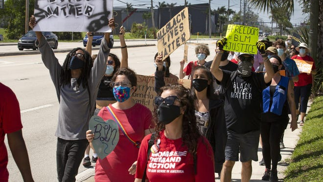 Protesters holding a March 4 Justice walk along Congress Avenue in suburban West Palm Beach Saturday, July 25, 2020, heading to the Palm Beach County Sheriff's Office where they held a rally. About 50 people showed up for the events, organized by Freedom Fighters 4 Justice.
