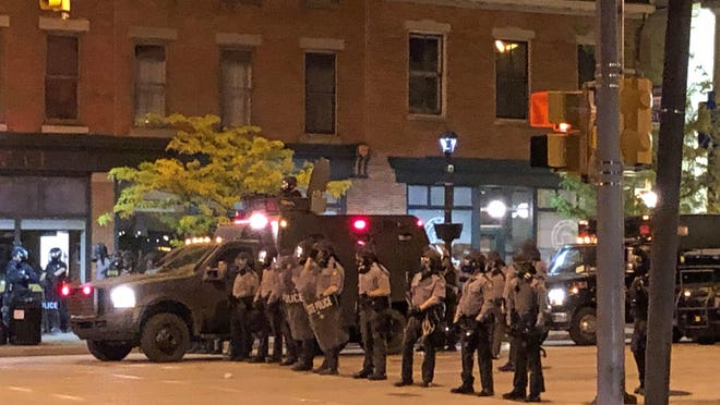 A Pennsylvania State Police riot team moves into in the 400 block of State Street after a riot broke out following a peaceful protest at Perry Square on Saturday night. Several neighboring law enforcement agencies assisted Erie police at the scene.