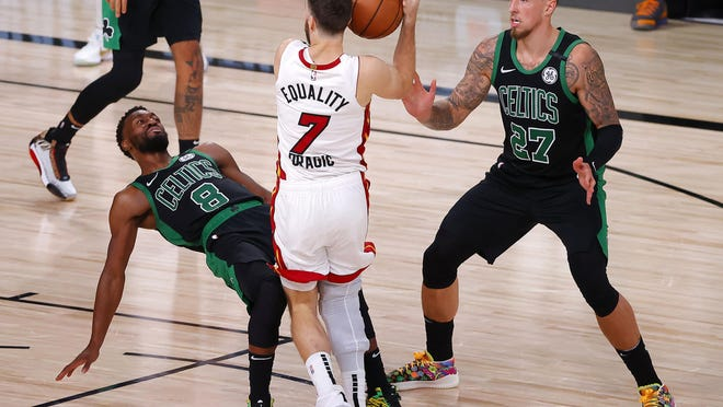 The Miami Heat's Goran Dragic (7) drives the ball against the Boston Celtics' Kemba Walker (8) and Daniel Theis (27) during the fourth quarter in Game 2 of the Eastern Conference Finals at AdventHealth Arena at the ESPN Wide World Of Sports Complex on Thursday, in Lake Buena Vista, Florida. The Heat won, 106-101, for a 2-0 series lead.
