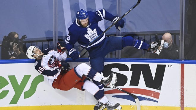 Maple Leafs left wing Kyle Clifford delivers a crushing hit to Blue Jackets defenseman Dean Kukan during the first period of Tuesday's game in Toronto.
