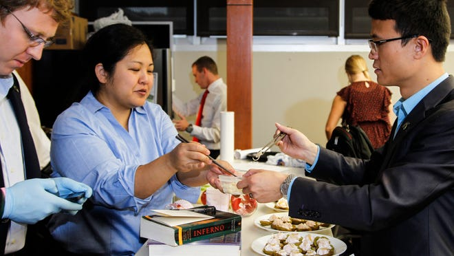 """From left.  MSU MBA students  Dmitri Alexandrov, left, double checks the spelling of """"Le petite choux,"""" a dessert their """"The Finer Things Club"""" made for MSU's MBA Cook-Off, while Tomomi Veki and Lei Zhu add finishing garnishes.  [Photo October 13, 2014 by MATTHEW DAE SMITH 