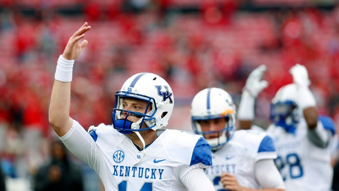 Kentucky's Patrick Towles and teammates pump up their fan section before the game. Nov. 29, 2014