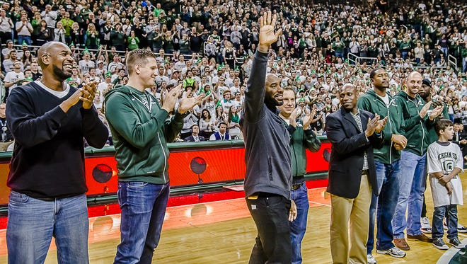Captain of the 2000 MSU Basketball National Championship team, Mateen Cleaves, waves to the crowd as the team is introduced at halftime of the MSU Men's game with Florida Saturday December 12, 2015 in East Lansing.  KEVIN W. FOWLER PHOTO
