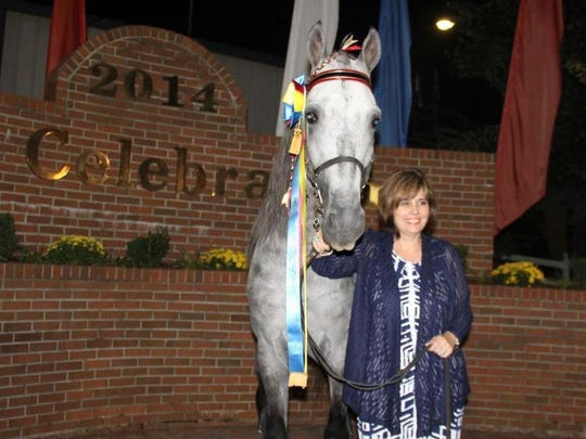 Carole Baxter stands in front of Jimmer Fredette after he won the Tennessee Walking Horse National Celebration 4-year-old World Grand Championship last August.