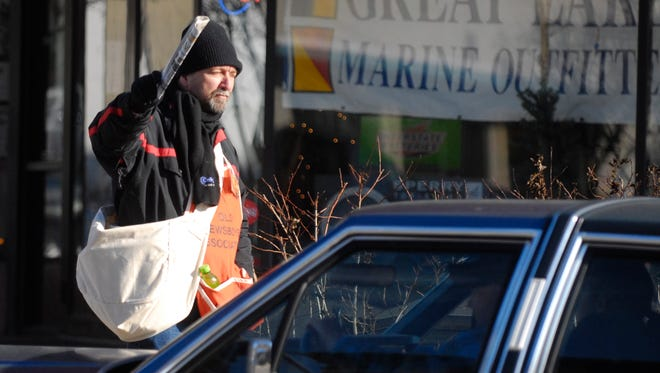Doug Wacker of Port Huron sells newspapers at the intersection Grand River and Huron in downtown Port Huron for Old Newsboys.