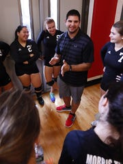 New Morris Tech volleyball coach John Lisella, 23, gives a pep talk a home match against Morris Catholic on Sept. 20.