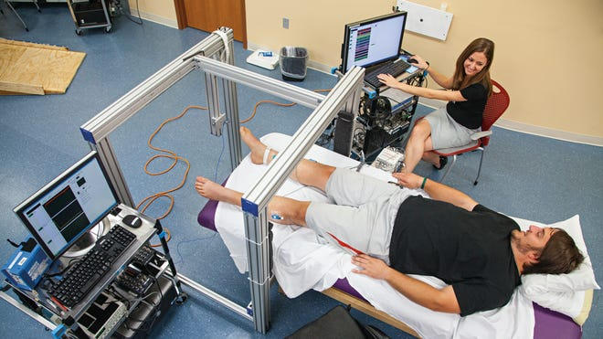 Kent Stephenson does voluntary training while Katelyn Gurley tracks his level of muscle activity and force at the Human Locomotion Research Center laboratory, a part of the University of Louisville's Kentucky Spinal Cord Injury Research Center.