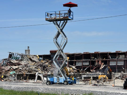 A safety officer watches over the demolition of the K-27 gaseous diffusion building continues Wednesday, April 20, 2016, as the U.S. Department of Energy (DOE) moves closer to fulfilling its Vision 2016. K-27 is the last of five gaseous diffusion facilities to be torn down at the East Tennessee Technology Park, the former Oak Ridge Gaseous Diffusion Plant. (MICHAEL PATRICK/NEWS SENTINEL)
