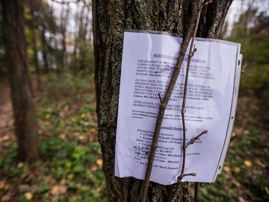 A notice is posted to a tree near a camp in the woods