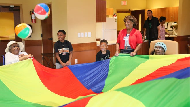 Children take part in activities in the adult day care area of St. Ann Center for Intergenerational Care.