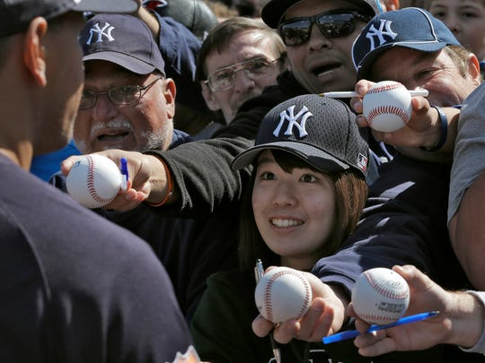 Fans mob New York Yankees' Alex Rodriguez, left, as